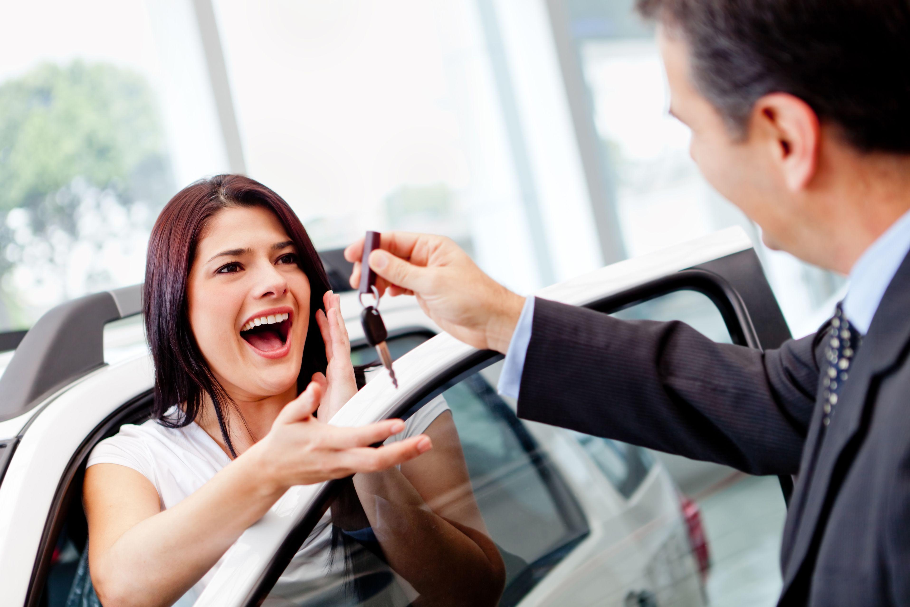 Девушка получает ключ от авто в салоне