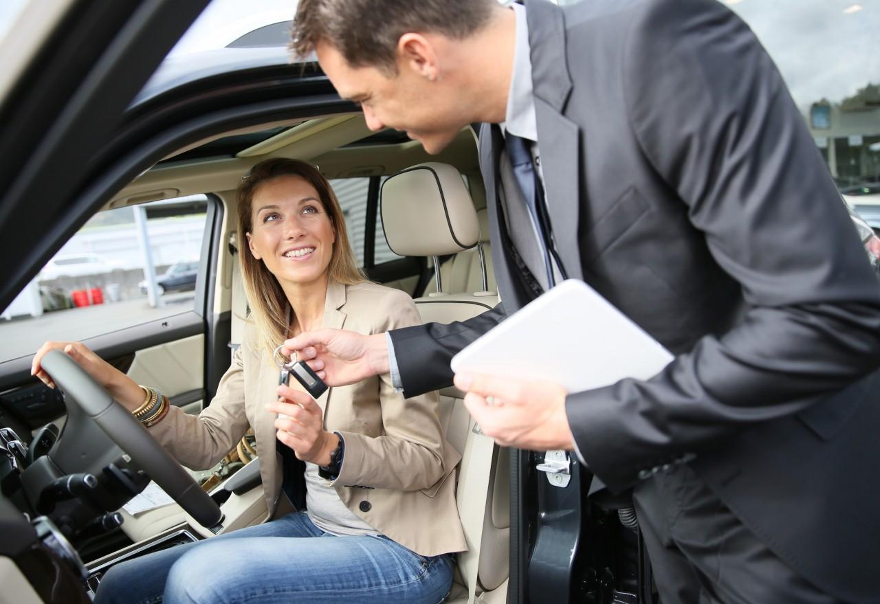 Менеджер вручает ключи новой владелице авто