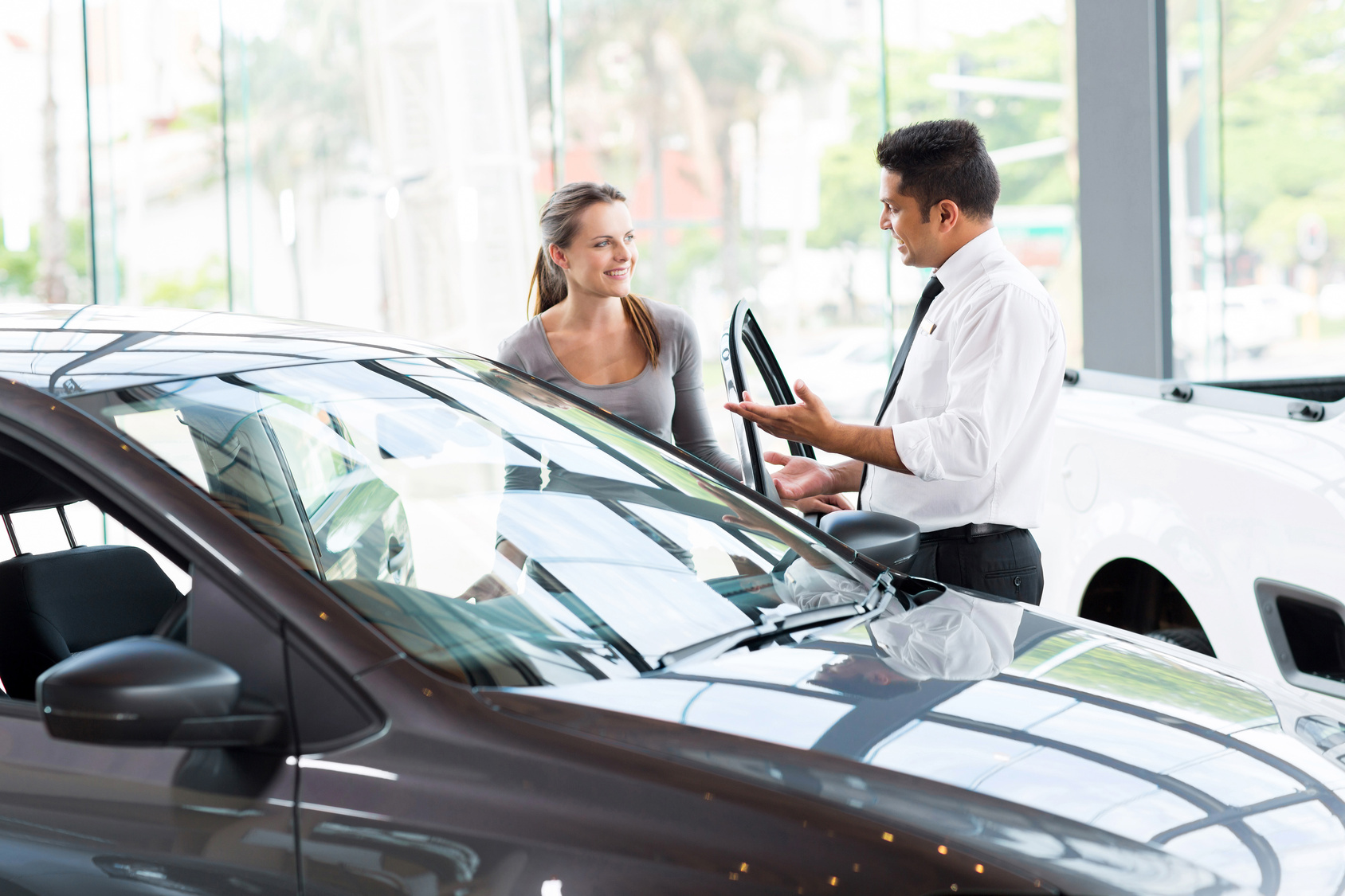 women buying cars Beautiful young women buying a car at dealership woman buying car young women buying a car in a showroom with sales assistant man woman buying car.